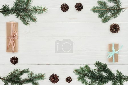 top view of evergreen coniferous branches, pine cones and christmas presents on white wooden background