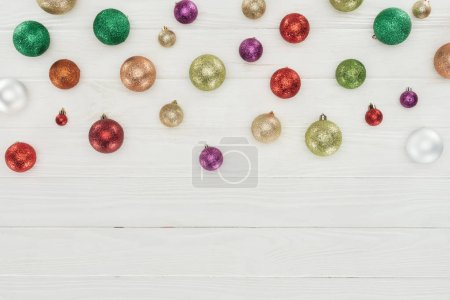 top view of beautiful shiny colorful christmas balls on white wooden background