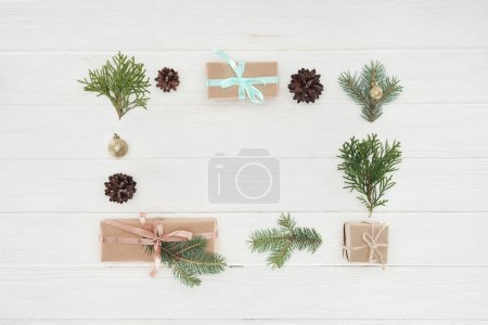 top view of christmas presents, shiny golden balls, pine cones and coniferous twigs on wooden background