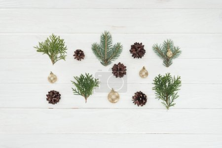 top view of shiny golden baubles, pine cones and evergreen coniferous branches on wooden surface