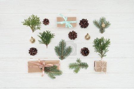 Photo pour Vue de dessus de Noël présente, branches de conifères à feuilles persistantes et des pommes de pin sur une surface en bois - image libre de droit
