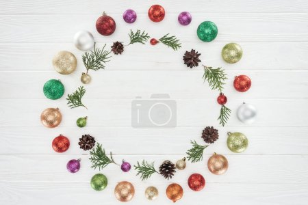 top view of beautiful shiny colorful baubles, coniferous twigs and pine cones on wooden surface, christmas background