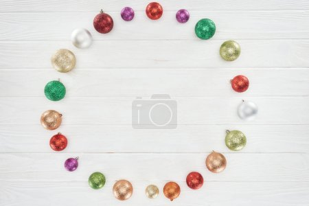 top view of beautiful shiny colorful baubles on wooden surface, christmas background