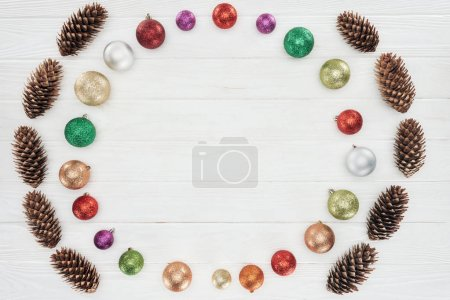 top view of beautiful shiny colorful baubles and pine cones on wooden surface, christmas background
