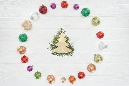Photo pour Vue de dessus de rameaux de conifères, symbole de l'arbre de Noël et boules brillants colorés sur la surface en bois - image libre de droit