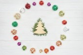 top view of coniferous twigs, christmas tree symbol and colorful shiny baubles on wooden surface