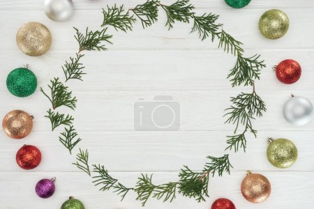 top view of round frame of coniferous twigs and shiny colorful baubles on wooden background
