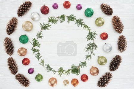 evergreen coniferous twigs, pine cones and shiny colorful baubles on white wooden background