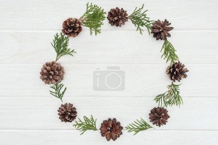 Photo pour Armature ronde faite de rameaux de conifères à feuilles persistantes et des pommes de pin sur un fond en bois blanc - image libre de droit