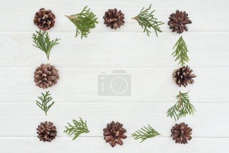 Photo pour Beau cadre, faite de rameaux de conifères à feuilles persistantes et des pommes de pin sur un fond en bois blanc - image libre de droit