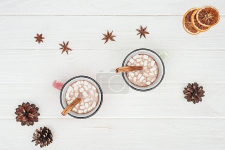top view of cups with hot chocolate and marshmallows, cinnamon sticks, star anise and pine cones on wooden table