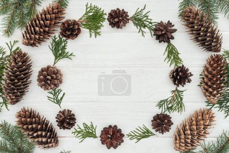 top view of evergreen coniferous twigs and pine cones on white wooden background