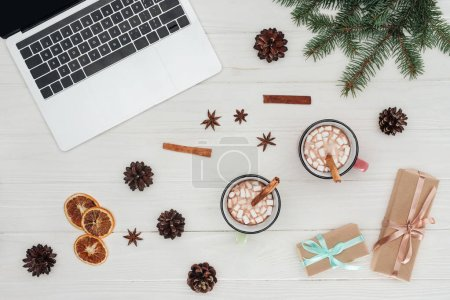 Photo for Flat lay with laptop, cups of hot chocolate and christmas presents on wooden table - Royalty Free Image