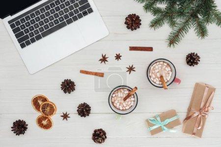 Foto de Lay Flat con laptop, tazas de chocolate caliente y la Navidad se presenta en mesa de madera - Imagen libre de derechos