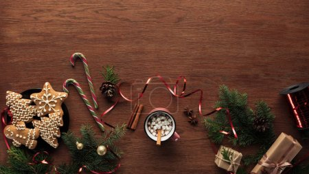 flat lay with cup of hot chocolate with marshmallows, cinnamon sticks and christmas decorations on wooden background