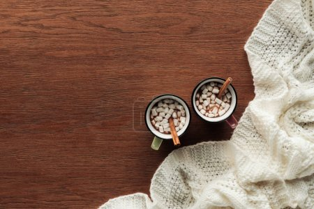 top view of mugs with delicious hot chocolate, marshmallows and cinnamon sticks on wooden background