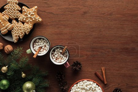 Photo for Flat lay with cups with hot chocolate, marshmallows and cinnamon sticks, tasty cookies and fir twigs with shiny baubles on wooden surface, christmas background - Royalty Free Image