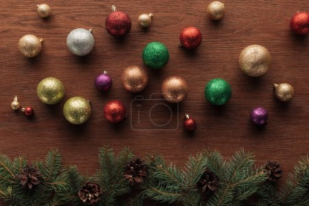 Photo pour Boules colorées brillantes et rameaux de conifères avec des pommes de pin sur fond en bois - image libre de droit