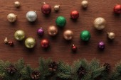 shiny colorful balls and coniferous twigs with pine cones on wooden background