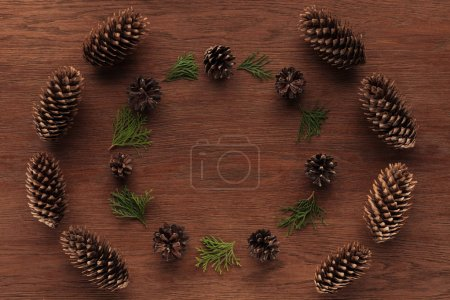 top view of beautiful evergreen coniferous twigs and pine cones on wooden background