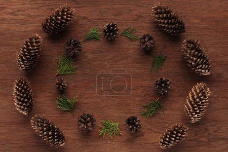 Photo pour Vue de dessus de belles rameaux de conifères à feuilles persistantes et des pommes de pin sur fond en bois - image libre de droit