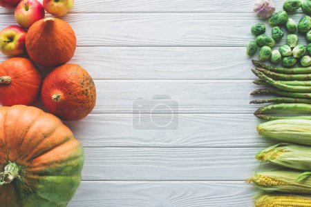 Photo for Top view of brussels sprouts, green asparagus, corn cobs, garlic and pumpkins on wooden table - Royalty Free Image