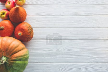 Photo for Top view of autumnal ripe pumpkins and apples on wooden tabletop - Royalty Free Image