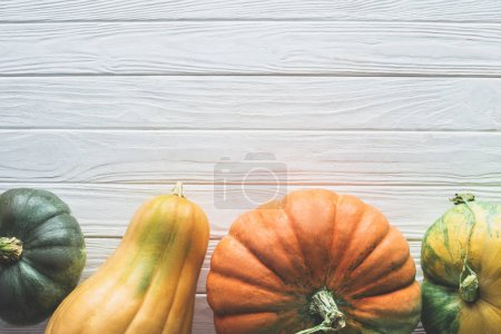 top view of green, yellow and orange pumpkins on tabletop