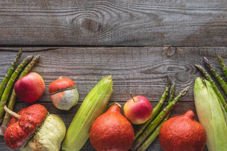 Photo for Top view of corn cobs, green asparagus, pumpkins and apples on grey wooden tabletop - Royalty Free Image