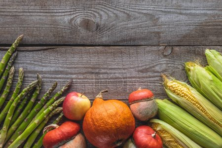 Photo for Elevated view of corn cobs, green asparagus, pumpkins and apple on grey wooden tabletop - Royalty Free Image