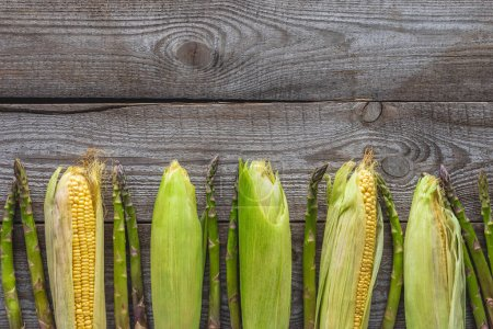 top view of ripe corn cobs and green asparagus on grey wooden tabletop