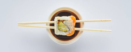 close-up view of delicious sushi and chopsticks with soy sauce in bowl isolated on white