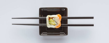 close-up view of tasty sushi and chopsticks isolated on white