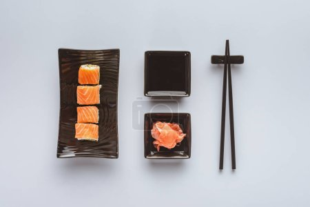 top view of delicious sushi with salmon, ginger, soy sauce and chopsticks isolated on white