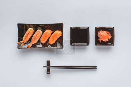 top view of gourmet sushi with salmon and shrimp, ginger and chopsticks isolated on white