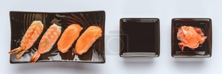 gourmet sushi with salmon and shrimp, ginger and soy sauce isolated on white