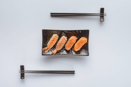top view of tasty sushi with salmon and shrimp on plate and chopsticks isolated on white