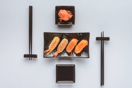 gourmet sushi with salmon and shrimp, ginger and chopsticks isolated on white