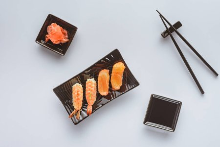 top view of tasty sushi with salmon and shrimp, ginger and chopsticks isolated on white