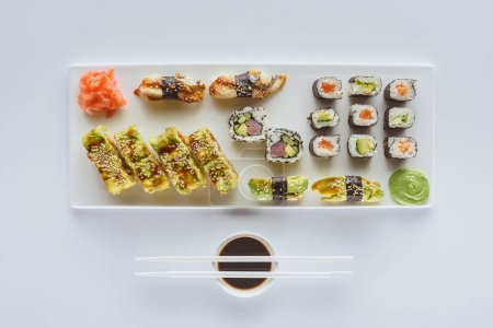 top view of gourmet sushi set with ginger, wasabi, soy sauce and chopsticks isolated on white