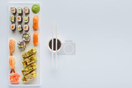 top view of delicious sushi set and soy sauce in bowl with chopsticks isolated on white background