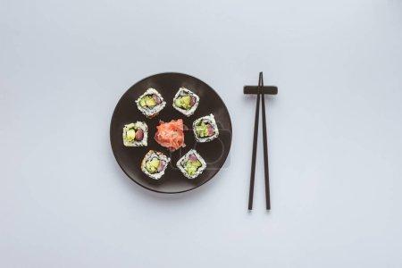 Photo pour Vue de dessus de délicieux sushis au gingembre sur plaque ronde et baguettes isolées sur blanc - image libre de droit