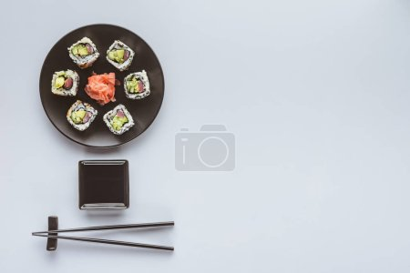 top view of delicious sushi with ginger and chopsticks isolated on white