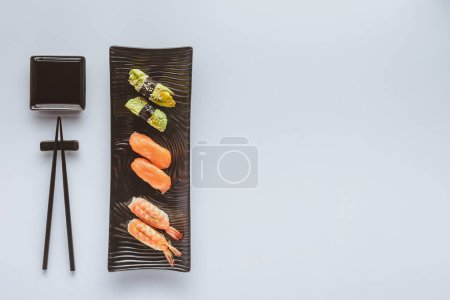 top view of delicious sushi set and chopsticks isolated on white