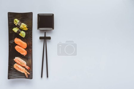 top view of various gourmet sushi and chopsticks isolated on white