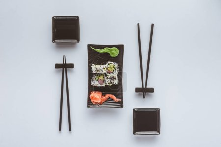 top view of gourmet sushi with chopsticks, ginger and wasabi isolated on white