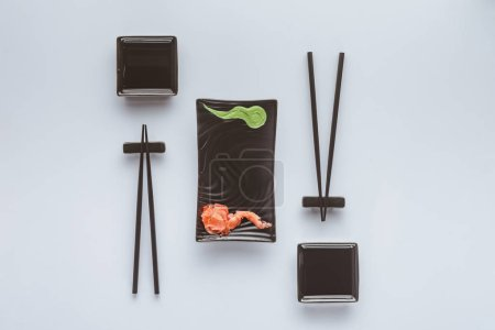 top view of chopsticks and wasabi with ginger for eating sushi isolated on white