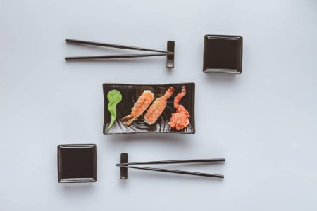 top view of gourmet sushi with shrimp, ginger and wasabi isolated on white