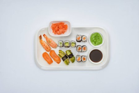 Photo for Top view of delicious sushi set with soy sauce, ginger and wasabi isolated on white - Royalty Free Image