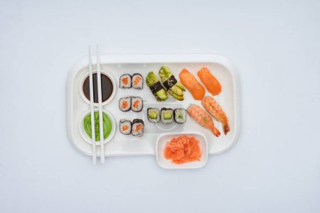 top view of gourmet sushi set with chopsticks isolated on white